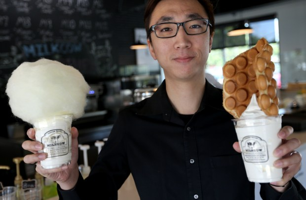 Cotton candy and egg puff-topped soft-serve ice creams held up by Milkcow Cafe co-owner Gordon Lai