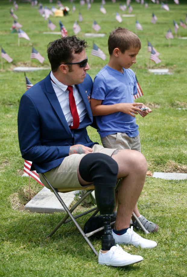 Jordan Stevenson, a member of a Navy explosive ordinance disposal unit who was injured in Afghanistan, talks to his son, Kayden Stevenson, 7, after a Memorial Day ceremony honoring veterans at Oak Hill Cemetery on Monday, May 29, 2017, in San Jose, Calif. (Jim Gensheimer/Bay Area News Group)