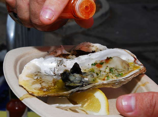 Phil Delano of Bethel Island douses his oysters with a dash of hot sauce at the 25th annual Pittsburg Seafood Festival in Pittsburg, Calif. on Saturday, Sept. 12, 2009. The popular event includes live music, vendors and plenty of seafood.(Sherry LaVars/Staff)