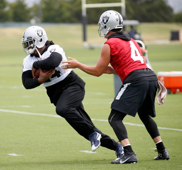 Oakland Raiders quarterback Derek Carr (4) hands off to running back Marshawn Lynch (24) during organized team activities at their headquarters in Alameda, Calif., on Tuesday, May 30, 2017. Carr said Tuesday if a contract extension isn't completed by the start of training camp, he will play out the final season of his original four-year deal. (Jane Tyska/Bay Area News Group)