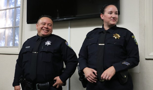 Atherton Police level one reserve officer Martin Mijangos, left, with his wife, Menlo Park Police Officer Victoria Trask, who had just pinned his badge on him after Mijangos was sworn in by Atherton Police Chief Steven D. McCulley at the Atherton City Council meeting on Wednesday, May 17, 2017. (John Orr / Daily News)