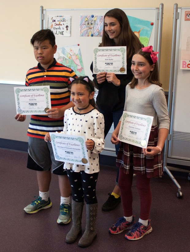 Winners of the Peninsula Humane Society & SPCA's Be Kind to Animals Art Contest pose with their certificates on Tuesday, May 9, 2017. In front, with the cat ears, is Ava Jean O'Donnell-Fernando, who attends school in San Bruno; at left is David Hu, who goes to school in Burlingame; in back is Kate Ryder, who attends school in Pacifica; and at right, with the pink bow, is Charlotte Graham, who attends school in Menlo Park. (Thelma Andree / Peninsula Humane Society)