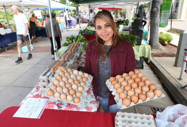Photograph by George SakkestadMartha Queiroz holds up dozens of fresh eggs she was selling at  Saratoga Village Wednesday Farmer's Market.