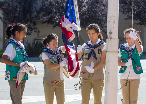File Photograph by Pietro Brezzo Saratoga honors military veterans with its 89th annual Memorial Day Observance beginning in Blaney Plaza with a procession to Madronia Cemetery on May 29. Pictured are members of Saratoga Girl Scouts Service Unit 618 raising the flags at Blaney Plaza to half-staff to start Saratoga's Memorial Day Observance in Saratoga in 2014.