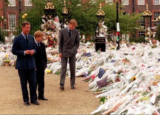 The Prince of Wales, left, and his sons Prince William, third from left, and Prince Harry, second from left, view the sea of floral tributes to their mother, Diana, Princess of Wales, at Kensington Palace, in background, Friday Sept. 5 1997. (AP Photos/Rebecca Naden/POOL)