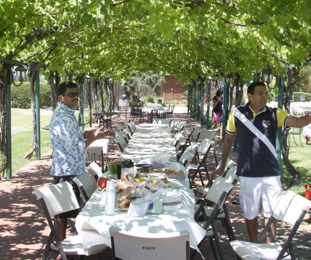 The Pamarthy and Ramesh families of Fremont set up for a picnic beneath a grapevine covered arbor at Concannon Vineyards in Livermore, Calif. on Sunday, June 3, 2012. (Jim Stevens/Staff)