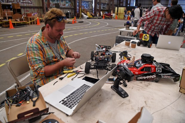Thomas Watson, of San Francisco, works on his car during a DIY Robocars event in Oakland, Calif. on Saturday, June 17, 2017. About 30 participants converged in a warehouse and attempted to get their mini self-driving vehicles to complete a lap on a makeshift road course. The monthly event started in January of this year. (Jose Carlos Fajardo/Bay Area News Group)