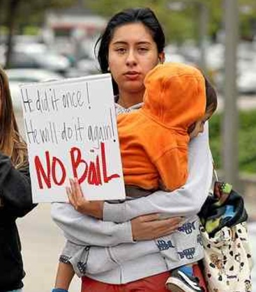 A woman holding her daughter protests outside Santa Cruz County Superior Court, where accused child molester and neurosurgeon James Kohut's bail was set at $6.4 million Wednesday. (Dan Coyro — Santa Cruz Sentinel)