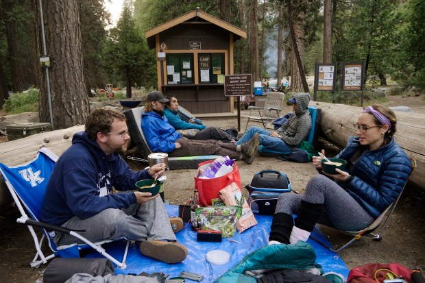 Roommates Austin Traut, at right, and Elise Adcock, both of Sunset Beach, Calif., hunker down for an overnight wait in hopes of getting a camp site the next morning at Camp 4 on Friday, May 26, 2017, at Yosemite National Park, Calif. (Jim Gensheimer/Bay Area News Group)