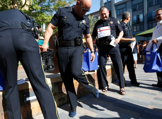 "San Jose Police Department Police Chief Eddie Garcia checks out his women's shoes as he prepares to walk for YWCA Silicon Valley's ""Walk A Mile In Her Shoes"" at Santana Row in San Jose, Calif. on Wednesday, June 21, 2017. Over 550 men walked in women's shoes to raise awareness and money to end violence against women. (Nhat V. Meyer/Bay Area News Group)"