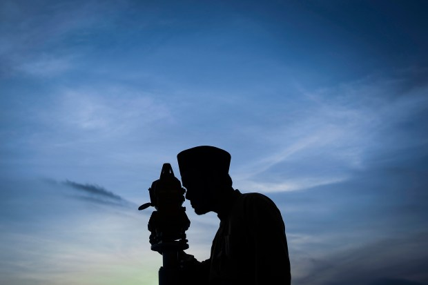 """In this July 16, 2015 file photo, a Malaysian Islamic authority performing the """"Rukyah Hilal Syawal,"""" the sighting of the new moon to determine the Eid Al-Fitr celebrations, is silhouetted against an early evening sky in Kuala Lumpur, Malaysia. The Eid al-Fitr celebrations start on Friday, July 17, which also marks the end of the Muslim holy fasting month of Ramadan. (AP Photo/Joshua Paul)"""
