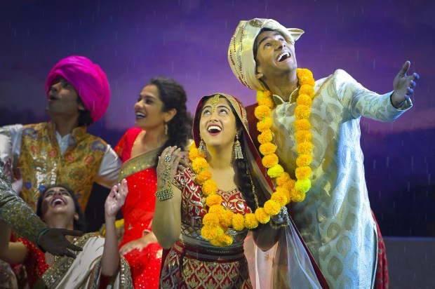"KEVIN BERNE/BERKELEY REPERTORY THEATRENewlyweds Aditi (played by Kuhoo Verma, second from right) and Hemant (Michael Maliakel, right) celebrate their new union amid a downpour in ""Moonsoon Wedding,"" getting its world premiere at Berkeley Repertory Theatre."