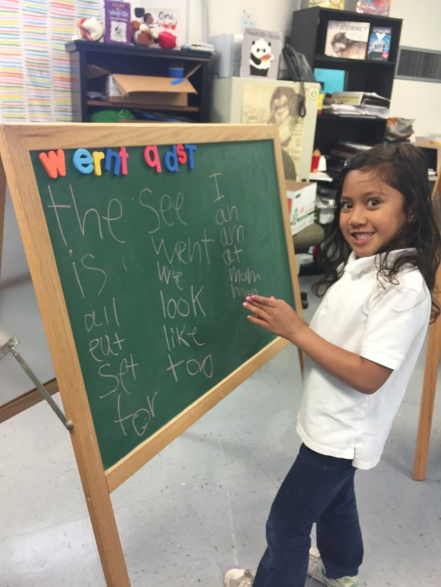 Arilana Mataafa, a kindergartner at Belle Haven School, stands next to a writing easel in reading teacher Rebecca Payne's classroom, after having written down all the words she knows and reading them back to Payne. (Rebecca Payne)
