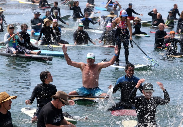 Surfers splash in the water during a paddle-out ceremony for Jack O'Neill near Pleasure Point in Santa Cruz, Calif., on Sunday, July 9, 2017. (Kevin Johnson/Santa Cruz Sentinel)