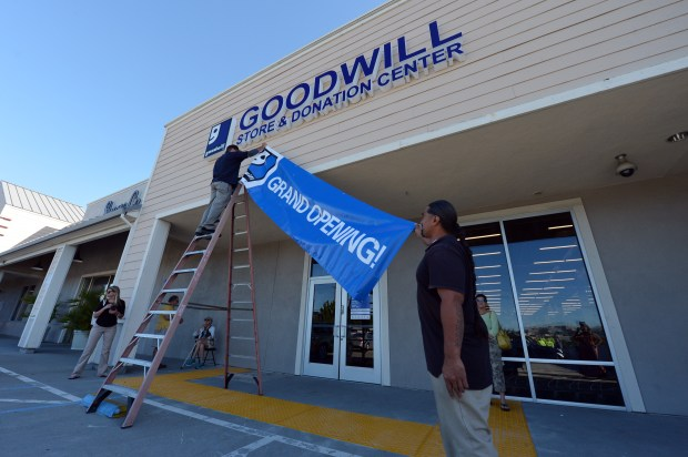 Workers hang a grand opening banner on the first day of business at the new Goodwill store in Walnut Creek, Calif. on Wednesday, July 12, 2017. (Kristopher Skinner/Bay Area News Group)