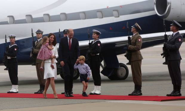 The Duke and Duchess of Cambridge with their children walks past honor guards during the arrival ceremony at the airport in Warsaw, Poland, Monday, July 17, 2017, at the start of their goodwill visit that is to stress Britain's friendly relations with the European Union nation amid London's bitter negotiations to leave the club. Prince William, his wife, the former Kate Middleton and their children, Prince George and Princess Charlotte will visit Warsaw and the Baltic coast city of Gdansk during their three-day trip to Poland. (AP Photo/Czarek Sokolowski)
