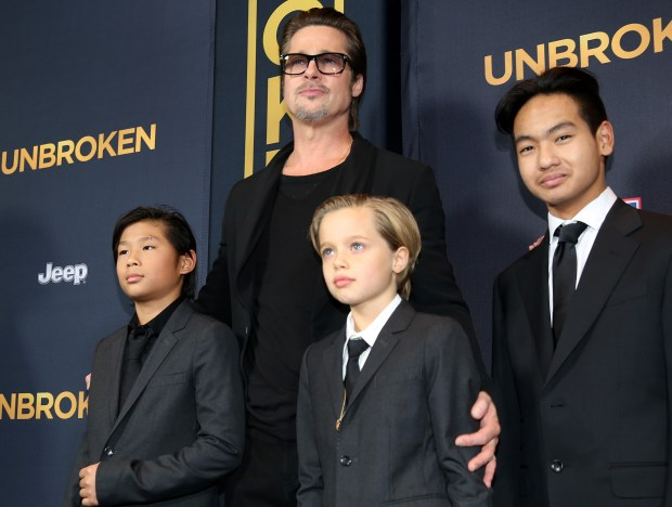 """Pax Jolie-Pitt, from left, Brad Pitt, Shiloh Jolie-Pitt and Maddox Jolie-Pitt arrive at the Los Angeles premiere of """"Unbroken"""" at TCL Chinese Theatre on Monday, Dec. 15, 2014. (Photo by Matt Sayles/Invision/AP)"""