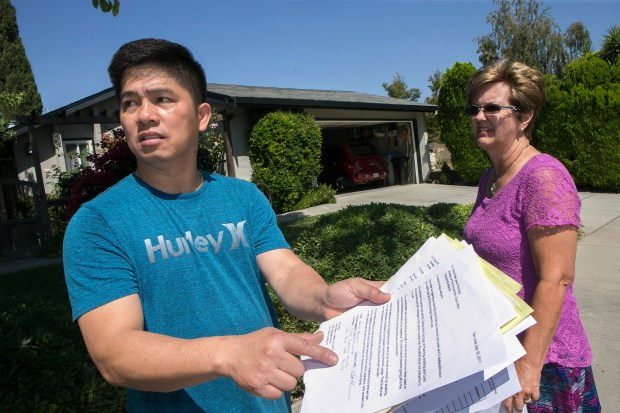 Michael Tran, left, shows his written response to a fireworks citation he received from the San Jose Fire Department for illegal fireworks in San Jose, California, on Wednesday, July 26, 2017. His neighbor Julie W. (no last name given), right, agreed to be a character reference in Tran's letter. (LiPo Ching/Bay Area News Group)