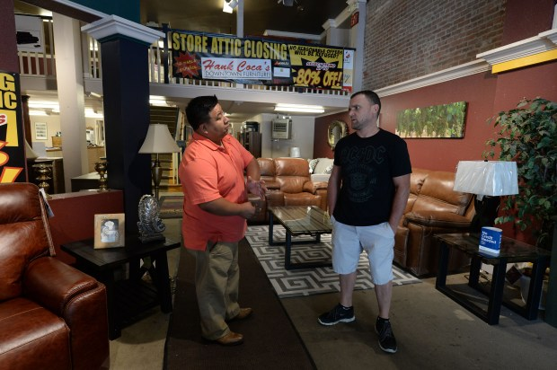 Store manager Rudy Lopez, left, talks with Josh McGhie, right, of San Jose, at Hank Coca's Downtown Furniture in downtown San Jose, Calif., on Wednesday, July 5, 2017. After 60 years of selling furniture, the retailer is closing, ending the reign as one of the oldest businesses. (Dan Honda/Bay Area News Group)