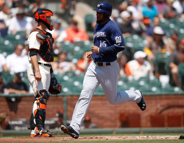Milwaukee Brewers' Domingo Santana (16) runs past San Francisco Giants' Buster Posey (28) after scoring a run in the first inning at AT&T Park in San Francisco, Calif., on Wednesday, August 23, 2017. (Nhat V. Meyer/Bay Area News Group)