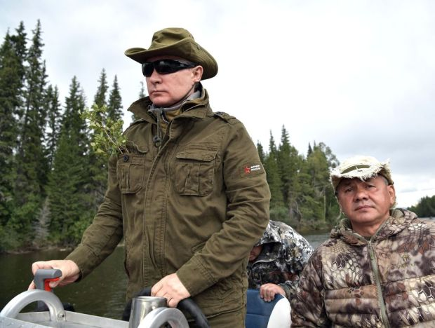 Russian President Vladimir Putin (L), accompanied by defence minister Sergei Shoigu, guides a boat during his vacation in the remote Tuva region in southern Siberia. The picture taken between August 1 and 3, 2017. / AFP PHOTO / SPUTNIK / Alexey NIKOLSKY (Photo credit should read ALEXEY NIKOLSKY/AFP/Getty Images)