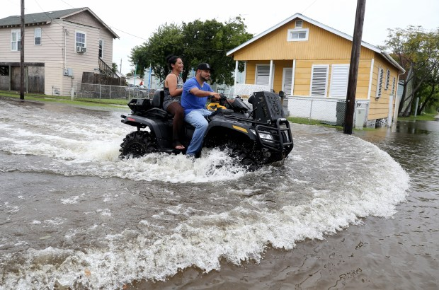 Galveston, Texas residents ride an all terrain vehicle down 50th Street on Saturday, Aug. 26, 2017, as they survey the flooding from Hurricane Harvey in their neighborhood. ( Jennifer Reynolds/The Galveston County Daily News via AP)