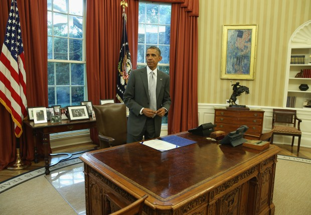 WASHINGTON, DC - AUGUST 04: U.S. President Barack Obama stands at his desk after signing the H.R.Res.76 Emergency Supplemental Appropriations Resolution in the Oval Office August 4, 2014 in Washington, DC. The bill gives emergency supplemental appropriations to provide funding for the Israeli Iron Dome defense. (Photo by Mark Wilson/)