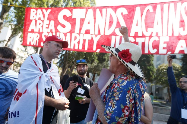 "Protestor Fred Dodsworth, right, argues with a man who is a President Donald Trump supporter, left, during the ""No to Marxism in America"" rally in Martin Luther King Jr. Civic Center Park on Sunday, Aug.27, 2017, in Berkeley, Calif. (Aric Crabb/Bay Area News Group)"