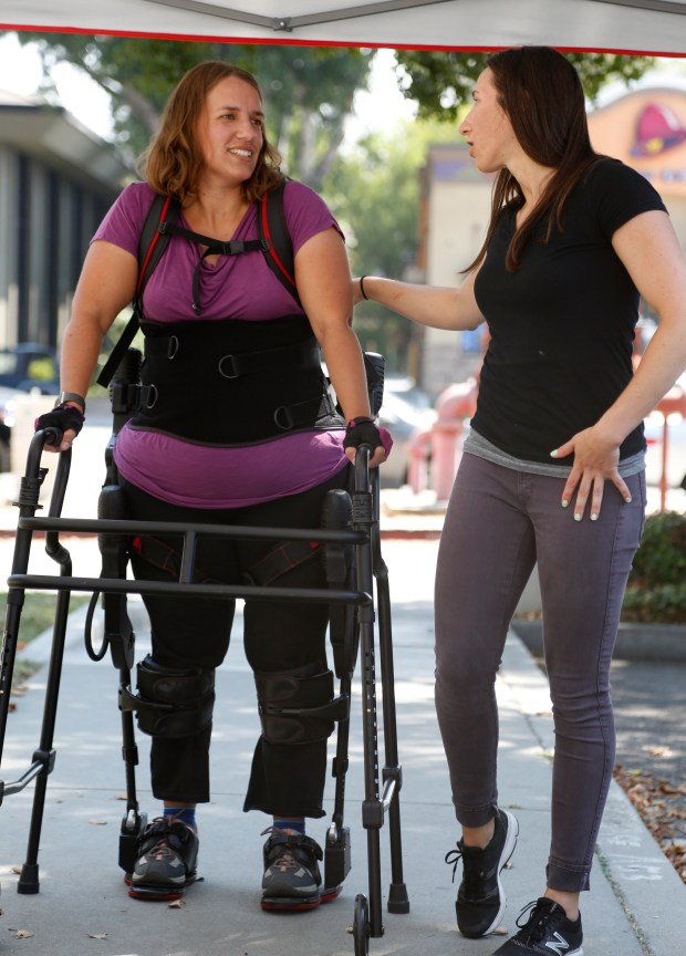 Michelle Southwick tries out an exoskeleton with the help of physical therapist, Jennifer Kapetanic, at Santa Clara Valley Medical Center in San Jose, California, Saturday, August 12, 2017. The medical center hosted an event for people with disabilities, their families and caregivers. Adaptive equipment, such as the exoskeleton, other robotic mobilizations devices, and motor vehicles were exhibited. Other highlights included a wheelchair dance class, accessible bocce ball, and hand cycle demonstrations throughout the event. (Patrick Tehan/Bay Area News Group)