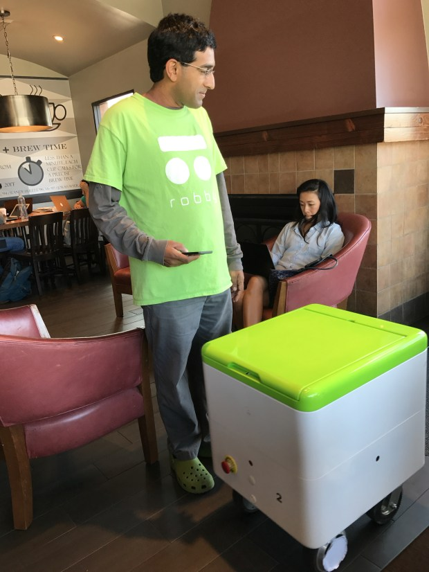 Dheera Venkatraman pilots a Robby Technologies prototype delivery robot toward the patio door at a Starbucks in Palo Alto on Monday, Aug. 28, 2017. (John Orr / Daily News)