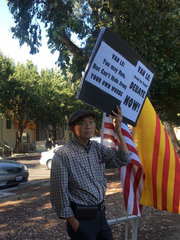 A supporter of Councilman Tam Nguyen holds up a sign during a press conference on Tuesday