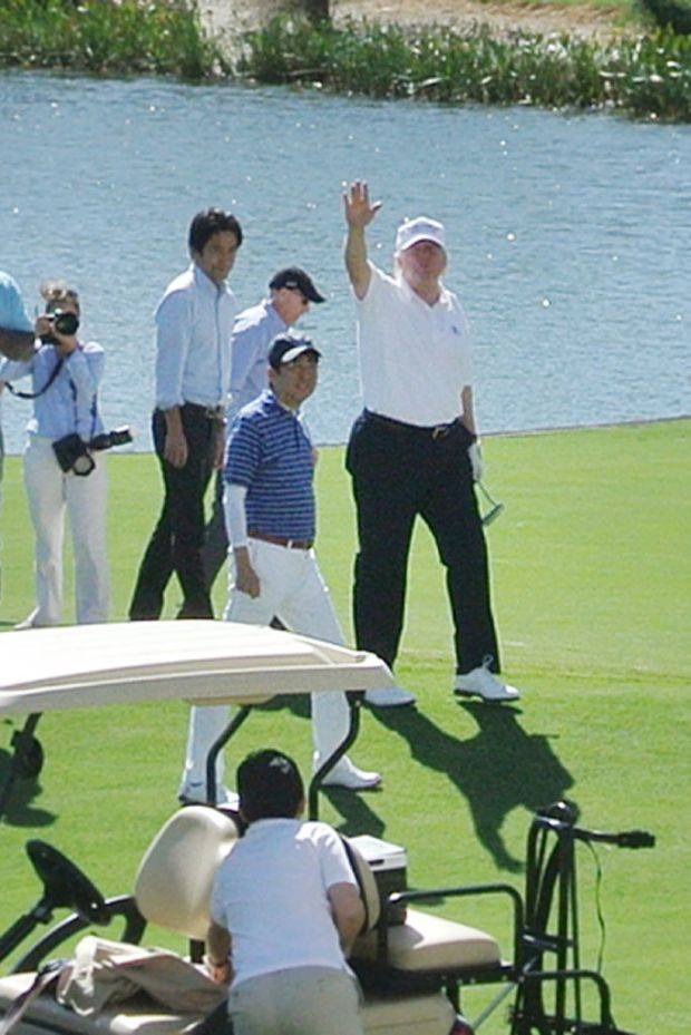 US President Donald Trump (R) waves beside Japan's Prime Minister Shinzo Abe (2nd R) while playing golf in Florida on February 11, 2017.After reportedly hitting it off in the Oval Office, President Donald Trump and his Japanese counterpart Shinzo Abe teed off on the golf course on February 11, and discussed US-Asia engagement. / AFP / JIJI PRESS / JIJI PRESS / Japan OUT (Photo credit should read JIJI PRESS/AFP/Getty Images)