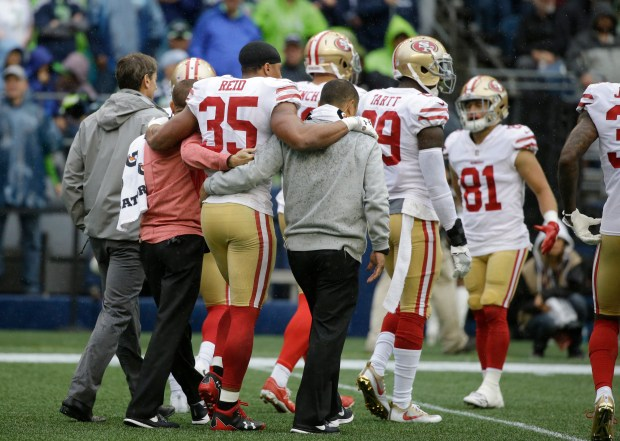 San Francisco 49ers strong safety Eric Reid (35) is helped off the field after an injury in the first half of an NFL football game against the Seattle Seahawks, Sunday, Sept. 17, 2017, in Seattle. (AP Photo/Elaine Thompson)