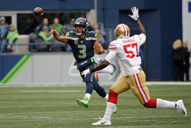 Seattle Seahawks quarterback Russell Wilson (3) passes under pressure from San Francisco 49ers outside linebacker Eli Harold in the first half of an NFL football game, Sunday, Sept. 17, 2017, in Seattle. (AP Photo/Elaine Thompson)