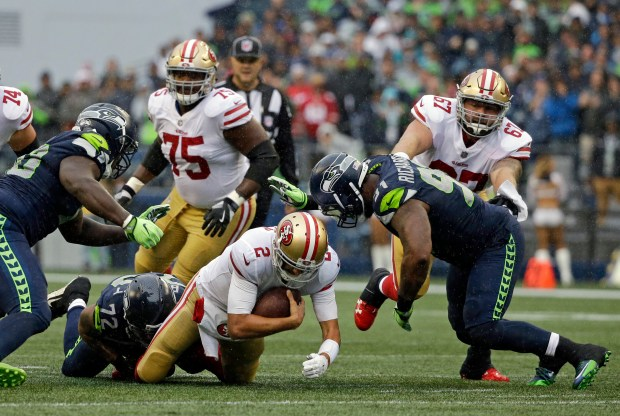 San Francisco 49ers quarterback Brian Hoyer (2) is tackled by Seattle Seahawks defensive end Michael Bennett (72) as Seahawks' Sheldon Richardson, lower-right, closes in during the first half of an NFL football game, Sunday, Sept. 17, 2017, in Seattle. (AP Photo/Elaine Thompson)
