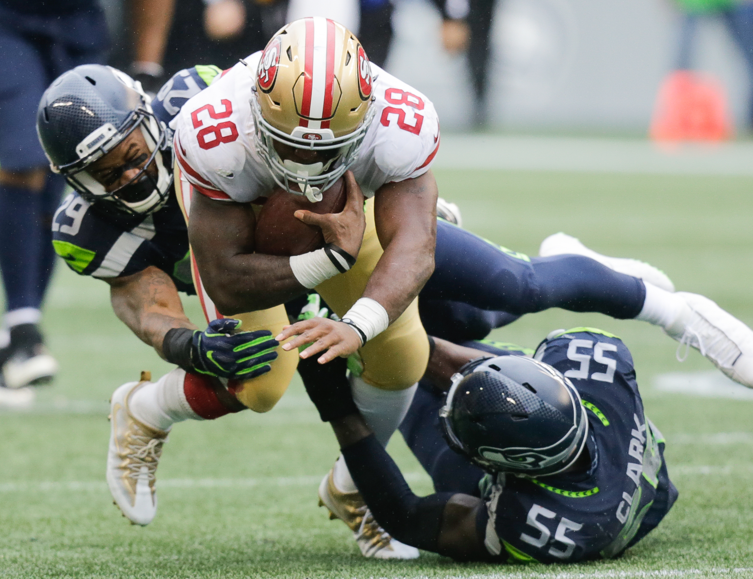 SEATTLE WA- SEPTEMBER 17 Running back Carlos Hyde #28 of the San Francisco 49ers is taken down by free safety Earl Thomas #29 of the Seattle Seahawks and defensive end Frank Clark #55 during the second half of the game at Century Link Field on September