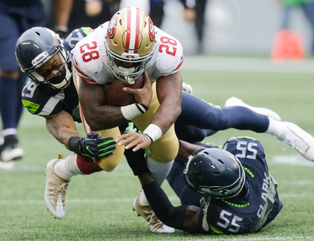 SEATTLE, WA - SEPTEMBER 17: Running back Carlos Hyde #28 of the San Francisco 49ers is taken down by free safety Earl Thomas #29 of the Seattle Seahawks and defensive end Frank Clark #55 during the second half of the game at CenturyLink Field on September 17, 2017 in Seattle, Washington. (Photo by Stephen Brashear/Getty Images)