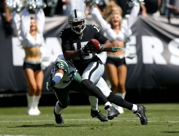 Oakland Raiders' Michael Crabtree (15) scores a touch down against New York Jets' Juston Burris (32) in the second quarter of their NFL game at the Oakland Coliseum in Oakland, Calif. on Sunday, Sept. 17, 2017. (Nhat V. Meyer/Bay Area News Group)