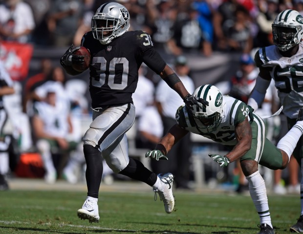 Oakland Raiders' Jalen Richard (30) outruns New York Jets' Juston Burris (32) to score a touchdown in the fourth quarter of their NFL game at the Oakland Coliseum in Oakland, Calif. on Sunday, Sept. 17, 2017. The Oakland Raiders defeated the New York Jets 45-20. (Jose Carlos Fajardo/Bay Area News Group)