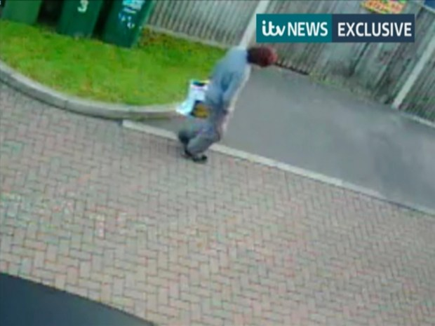 This image from video shows a person in Sunbury, England, on Friday, carrying the same type of shopping bag that held the bomb found on the train. (ITN via AP)