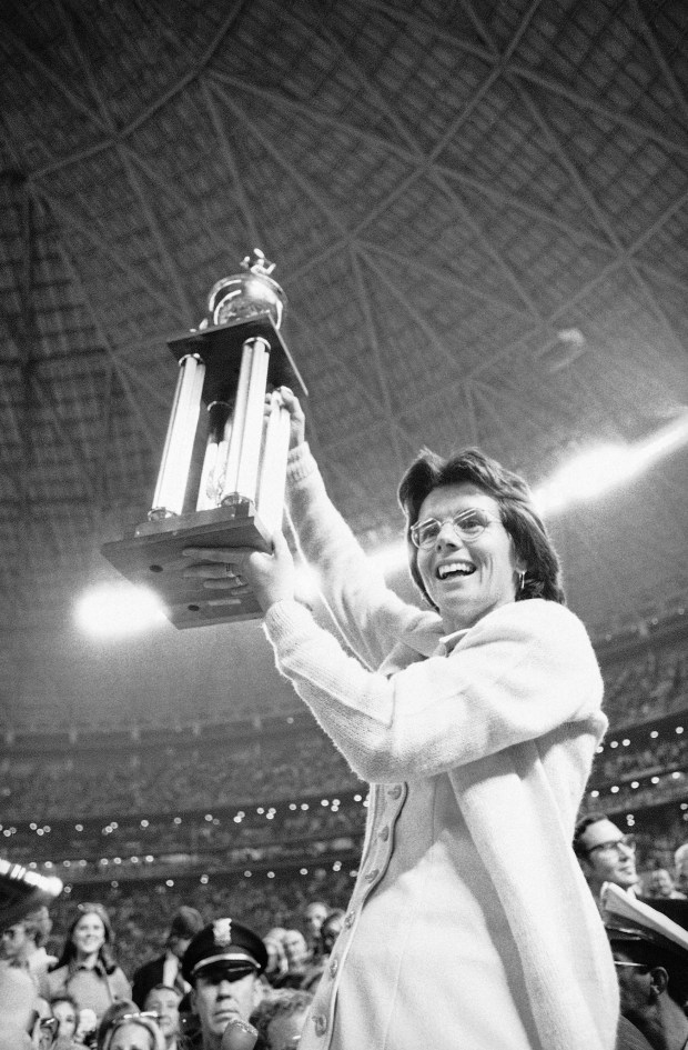 In this Sept. 20, 1973, photo Billie Jean King holds the winner's trophy high in the air after defeating Bobby Riggs in their $100,000 winner-take-all tennis match. (AP Photo/File)