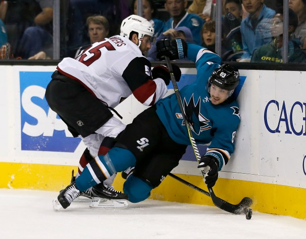 San Jose Sharks left wing Mikkel Boedker (89) is checked into the boards by Arizona Coyotes defenseman Jason Demers (55) during the second period of a preseason NHL hockey game, Saturday, Sept. 30, 2017, in San Jose, Calif. (AP Photo/Tony Avelar)