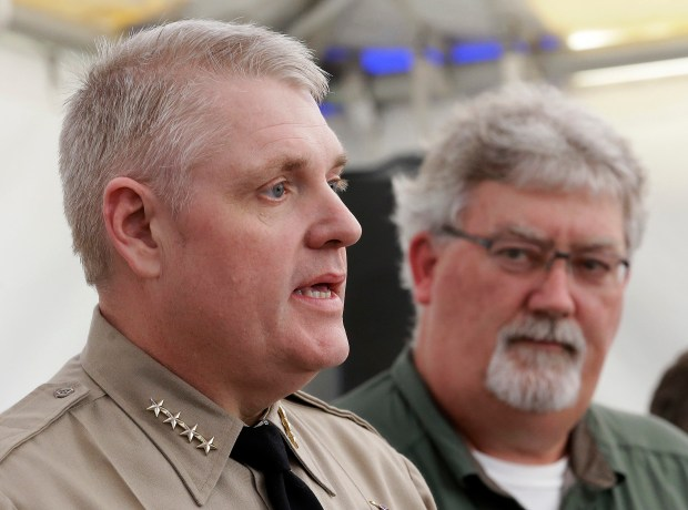 FILE - In this Feb. 14, 2017, file photo, Butte County Sheriff Kory Honea, left, answers a question concerning his decision to lift the evacuation order and allow people to return home, as Bill Croyle, acting director of the Department of Water Resources, right, looks on during a news conference in Oroville, Calif. Over six straight days, the operators of the Oroville Dam had been saying there was no immediate danger after water surging down the main spillway gouged a hole the size of a football field in the concrete chute. But now suddenly they realized that the dam's emergency backup spillway — essentially an unpaved hillside — was falling apart, too, and could unleash a deadly torrent of water. Honea reacted by ordering the immediate evacuation of nearly 200,000 people downstream. (AP Photo/Rich Pedroncelli, File)