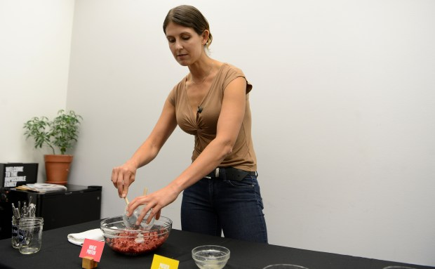 "Celeste Holz-Schietinger, PhD, demonstrates mixing the ingredients to make Impossible Burgers during a demonstration at the Impossible Foods offices in Redwood City, Calif., on Tuesday, Sept. 12, 2017. The company has developed a meatless ""burger"" that is currently being sold in some restaurants and recently opened a production facility in Oakland. (Dan Honda/Bay Area News Group)"