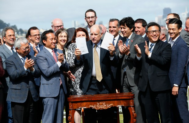 Gov. Jerry Brown is joined by state officials after he signed legislation for a package of 15 bills to address the state's housing affordability crisis at a ceremony in San Francisco, California, on Friday, Sept. 29, 2017. (Gary Reyes/ Bay Area News Group)