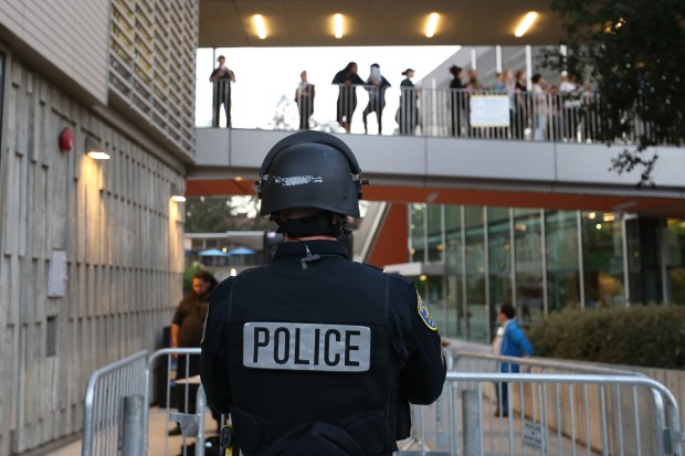 A police officer stands guard as peaceful demonstrators protests before conservative commentator Ben Shapiro speaks at UC Berkeley's Zellerbach Hall in Berkeley, Calif., on Thursday, Calif., on Thursday, Sept. 14, 2017. Security barricades were installed around the campus to prevent another violent protest like in last February when conservative Milo Yiannopoulos event was force to cancel. (Ray Chavez/Bay Area News Group)