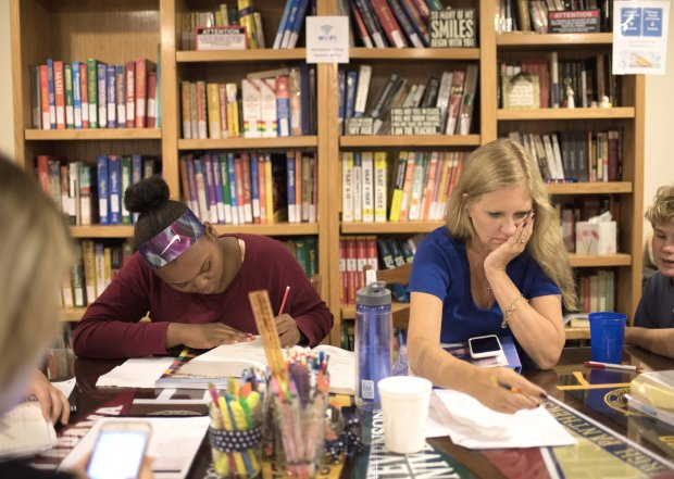 Lauren Dent, left, an eighth-grade middle schooler, studies while Rosschecks a client's work. Ross went into business for herself after having to leave a career for health reasons. (Reza A. Marvashti for The Washington Post)