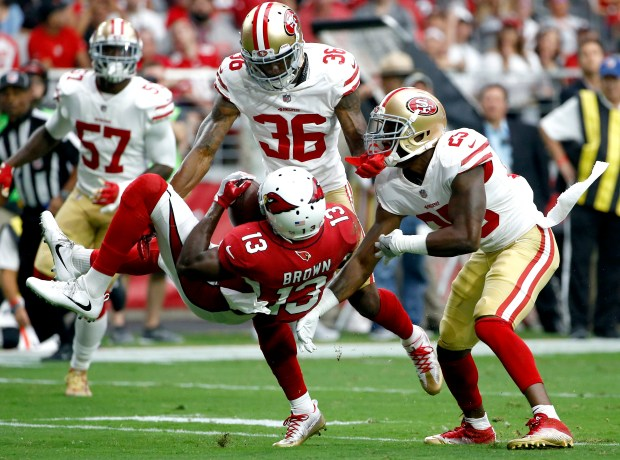 Arizona Cardinals wide receiver Jaron Brown (13) is hit by San Francisco 49ers cornerback Jimmie Ward (25) and cornerback Dontae Johnson (36) during the first half of an NFL football game, Sunday, Oct. 1, 2017, in Glendale, Ariz. (AP Photo/Ross D. Franklin)