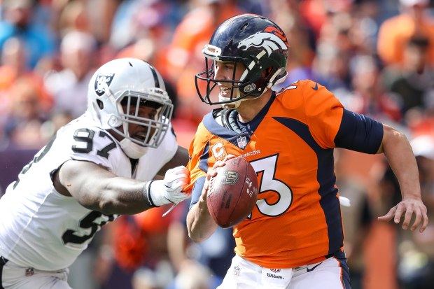 Quarterback Trevor Siemian #13 of the Denver Broncos is sacked by defensive end Mario Edwards #97 of the Oakland Raiders in the first quarter of a game at Sports Authority Field at Mile High on October 1, 2017 in Denver, Colorado. (Photo by Matthew Stockman/Getty Images)