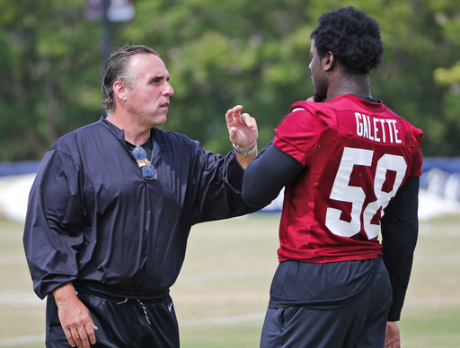 Washington Redskin defensive line coach, Jim Tomsula, talks with linebacker Junior Galette (58) during practice at the Washington Redskins NFL training camp in Richmond, Va., Wednesday, Aug. 2, 2017. (AP Photo/Steve Helber)